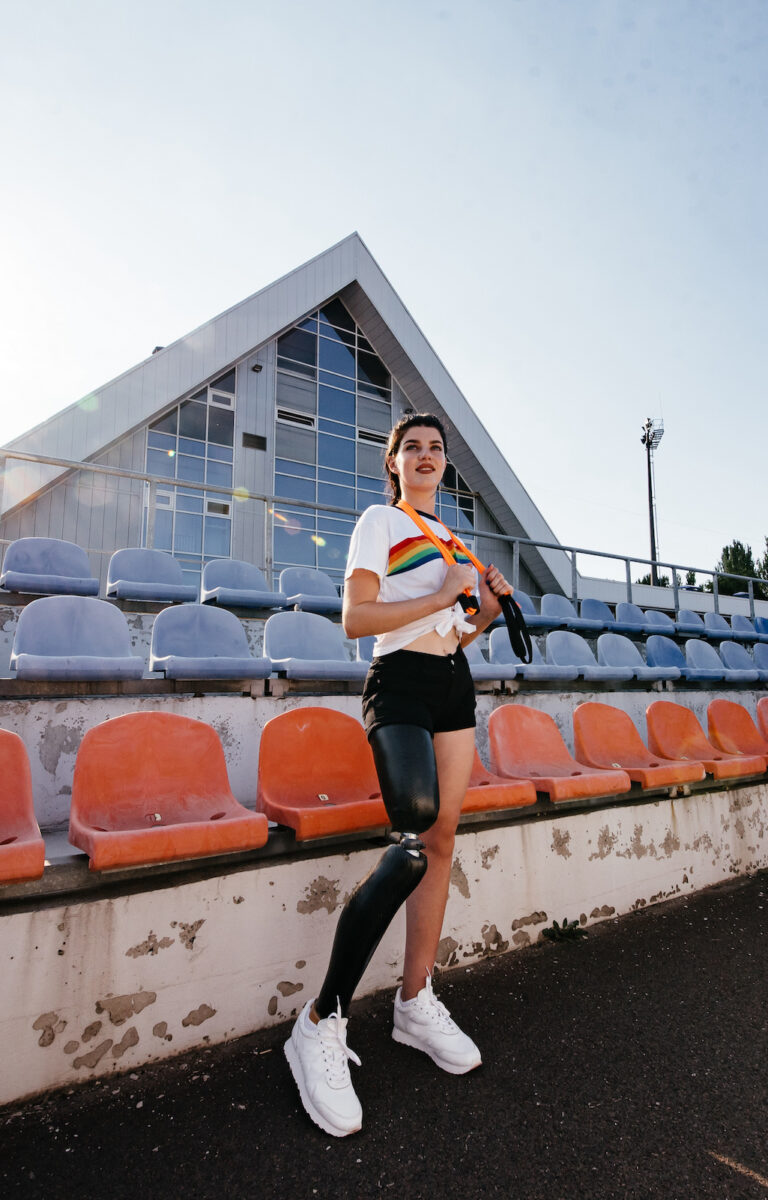 Photo of athletic disabled girl with bionic leg in sportswear standing and smiling outdoor over concrete wall